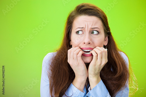 Anxiety. Scared woman biting fingernails, green background