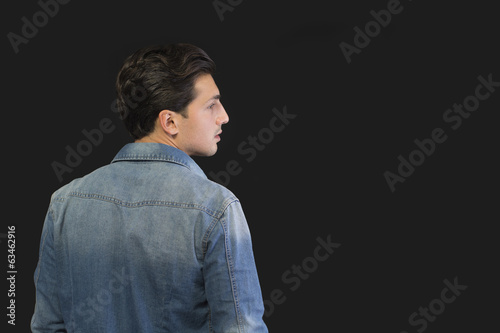 Young man w denim shirt seen from the back, looking to a side