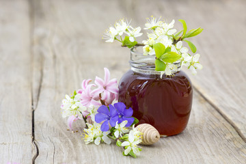 Honey in a jar, flowers and honey dipper on wooden background
