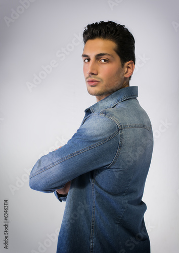 Young man wearing denim shirt, arms crossed on chest