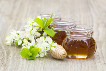 Honey in jars, flowers and honey dipper on white background
