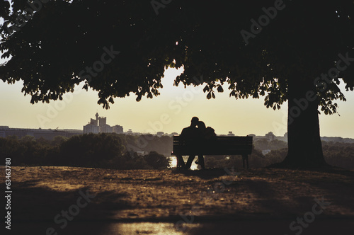 Embracing couple on a bench sunset