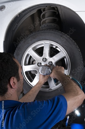 Car mechanic removing wheel nuts to check brakes