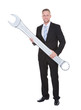Businessman in a smart suit holding a large metal spanner
