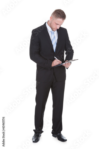 Businessman standing writing on a handheld clipboard