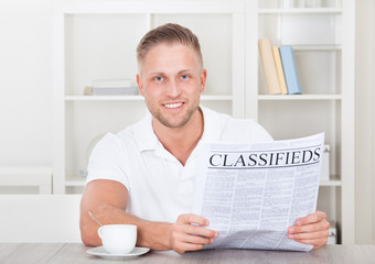 Excited man reading the classifieds