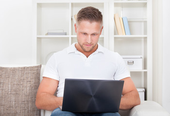 Young man sitting in his living room on the sofa using a laptop