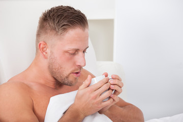 Man drinking hot tea in bed