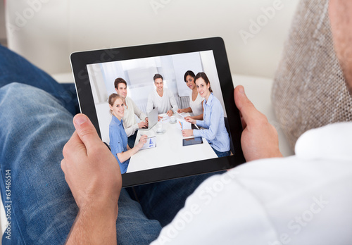 Businessman on a video call chatting to colleagues