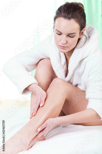 Woman rubbing lotion on her legs