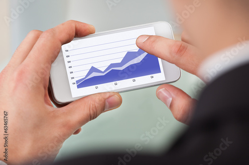Businessman Analyzing Graph On Smart Phone