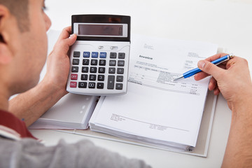 Man Calculating Financial Expenses At Home