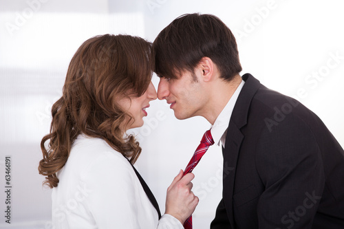 Businesswoman Pulling Male Colleague's Tie While Seducing Him