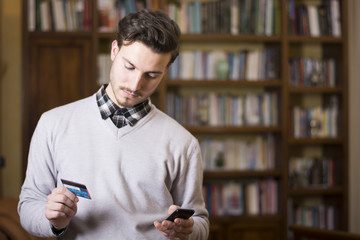 Handsome young man shopping online on mobile phone