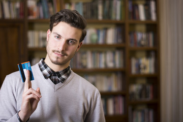 Attractive young man holding credit card, looking at camera