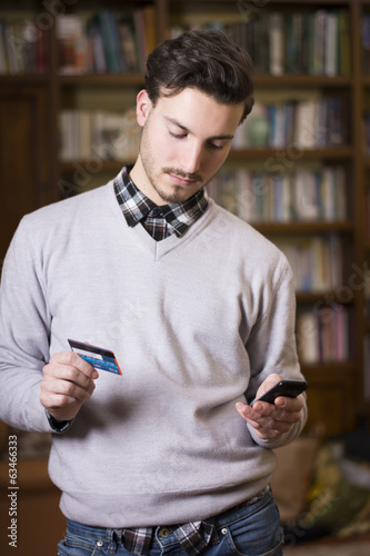 Attractive young man shopping online on mobile phone