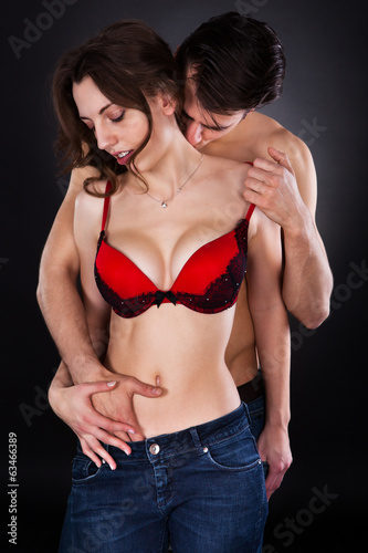 Man Inserting Hand In Woman's Jeans While Kissing On Neck
