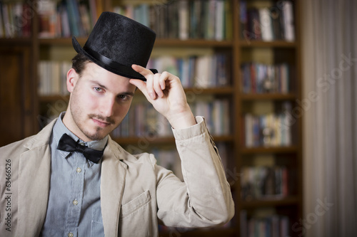 Elegant young man wearing top hat and bow tie