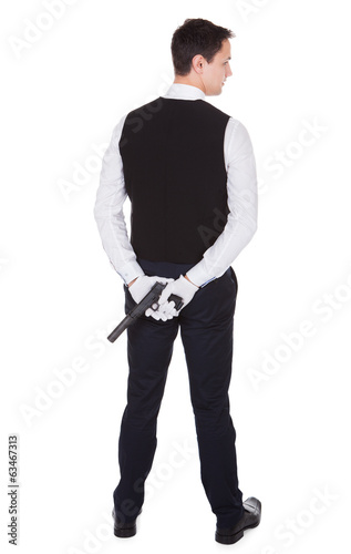 Rear View Of Waiter Holding Handgun