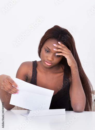 Depressed Woman Holding Bill At Table