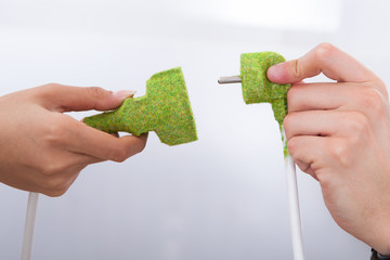 Hands Fixing Green Plugs
