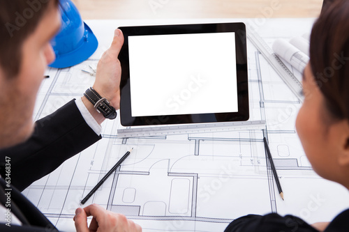 Architects With Digital Tablet Working On Blueprint