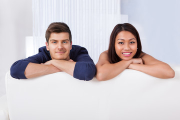 Smiling Young Couple Leaning On Sofa