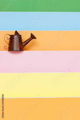 old and rusty watering can with colorful wood background