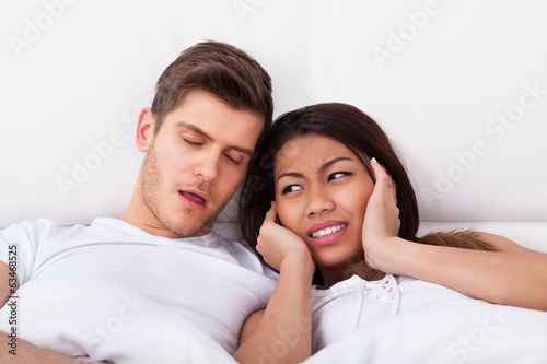 Irritated Woman Covering Ears While Man Snoring In Bed