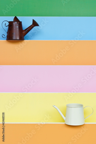 old and new watering can with colorful wood background