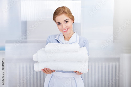 Maid Holding Stack Of Towels