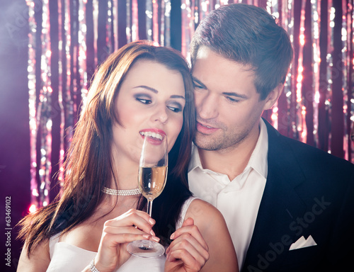 Couple Enjoying Champagne At Nightclub
