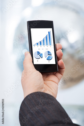 Hand Analyzing Financial Charts On Smartphone