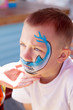 Boy painting face with shark