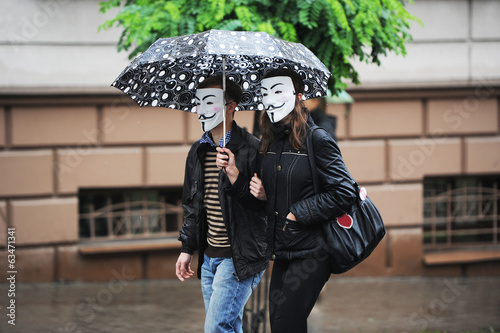 people in masks under umbrellas