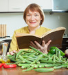 woman cooking okra with  cookbook in  kitchen