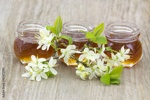 Honey in jars and flowers on wooden background