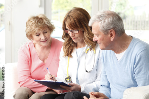 Elderly couple consulting with female doctor