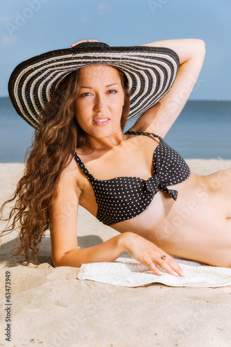 Woman in bikini lying down and sunbathing on the beach