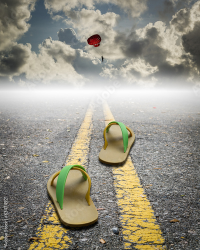 a pair of sandal on the road with parachute on the sky
