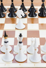 white knight in front of black chess