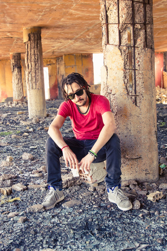 Guy with dreadlocks sitting on the rock
