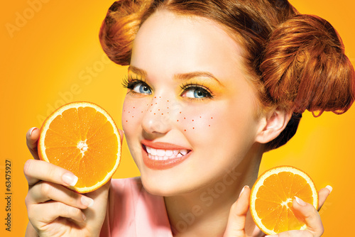 canvas print picture Beauty model girl with juicy oranges. Freckles