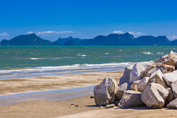 Big rock on beach and mountain background