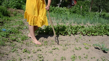 Barefoot girl in yellow dress grub weeds with hoe in garden