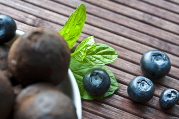 Chocolate truffles with blueberry and mint on wooden background
