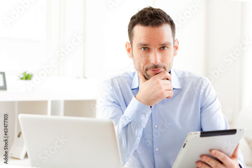 Young business man working at home on his tablet