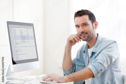 Portrait of a young relaxed man using computer