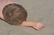 little boy lying on the sand