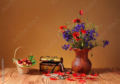 Cherries, jewelry and flowers in a vase